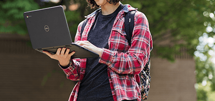 Student standing with laptop
