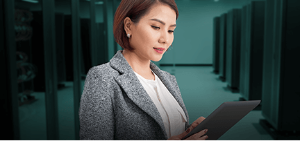 Photo of woman in a datacenter holding and working on a tablet